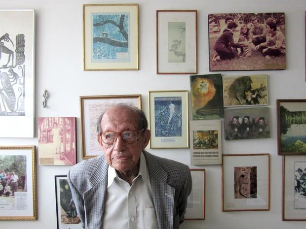 Pesquisador Milton Thiago de Mello em frente a uma parede com memórias de sua carreira (Foto: Alexandre Bastos/G1)